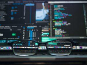 a closeup shot of a black eyeglasses facing at a computer with codes